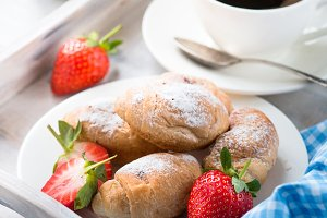 Mini croissants with berries and coffee.