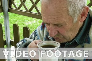 Senior elderly man eats and drinks tea on patio