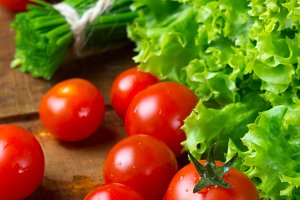 Fresh lettuce and tomatoes on wooden background