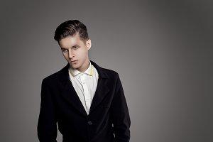Young trendy man. Black suite, gray background. Portrait