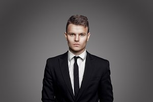 Young trendy man. Black suite and tie, gray background. Portrait