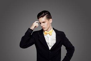 Young trendy man. Black suite, yellow bowtie, gray background. Portrait