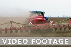 Tractor ploughs tills plows and seeds on the field