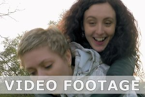 Two cheerful girls friends fools in park outdoors