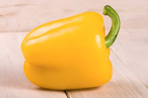 yellow sweet pepper on white wooden background