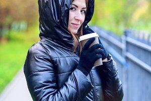 Girl in jacket with hood, holding a coffee or tea, young enjoys the outdoors and sports, spring  autumn, lifestyle, black , smiling brunette in gloves