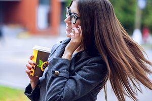 Girl in jacket talking on the phone, emotionally, holding a coffee or tea, young enjoys the outdoors and sports, spring  autumn, lifestyle, lunch Concept