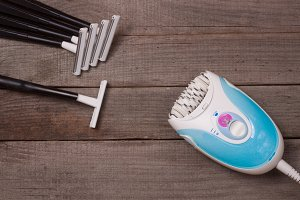 electric epilator with razor on a light wooden background