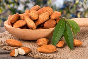 heap of peeled almonds with leaf in a wooden spoon on table blurred garden background