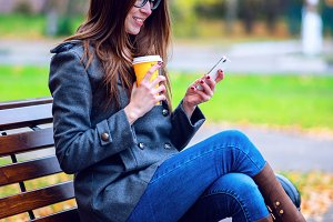 Girl reads sms, rewritten smartphone outdoors in spring or autumn, on the bench, with coffee  tea, breakfast, concept, glasses, urban fashion, lifestyle, brunette. Happy smiling.