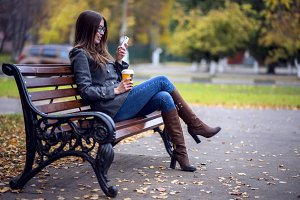 Girl reads sms, rewritten smartphone outdoors in spring or autumn, on the bench, with coffee  tea, breakfast, concept, glasses, urban fashion, lifestyle, brunette.