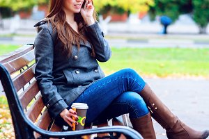 Girl in jacket talking on the phone, sitting  a bench, holding  coffee or tea,  young outdoors, spring  fall, life style, the concept of the city, lifestyle, listening to the conversation.