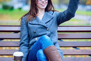The girl in the jacket makes selfie photo, sitting on a bench with glasses, holding  coffee or tea,  young outdoors, spring  fall, life style, the concept of the city, lifestyle, smile, happy. For social networks.