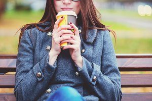 Beautiful young woman sitting on a bench drinking coffee or hot tea in the spring  autumn coat enjoying in park outdoors, glasses, urban life, the concept of breakfast in nature
