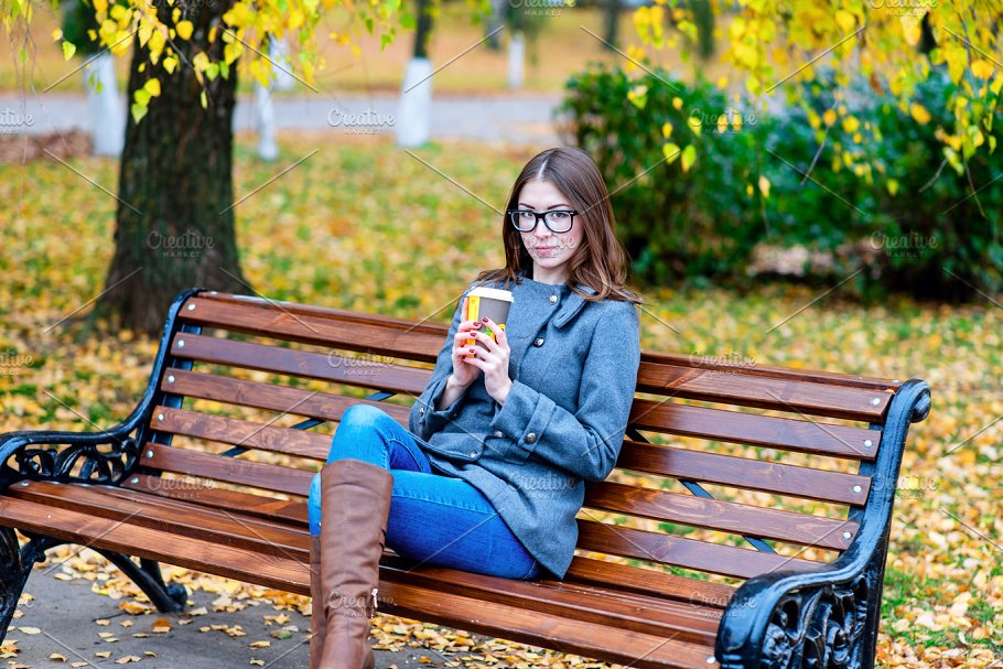 Beautiful Young Woman Sitting On A Bench Drinking Coffee Or Hot Tea In The Spring Autumn Coat Enjoying In Park Outdoors Glasses Urban Life The
