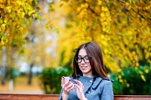 Girl in jacket sitting on the bench with glasses, holding a coffee or tea,  young outdoors, spring  fall, life style, the concept of the city, lifestyle, smile, happy.  the phone in hand.