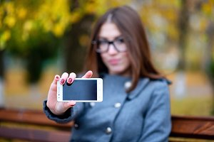 Beautiful young woman with glasses, in the spring, outdoors in the park in autumn coat the air, shows the phone in his hand, urban life, the concept of the text, your smartphone advertising, the idea   brand, blurred background