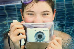 teen girl in swimming pool with underwter camera