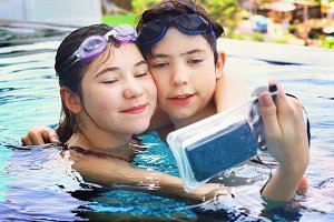 kids with underwater camera in swimming pool
