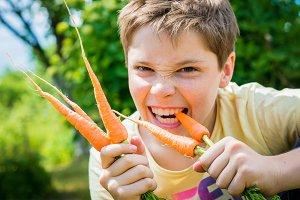 Teen boy eating a carrot