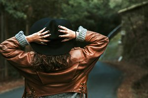 woman holding the hat back