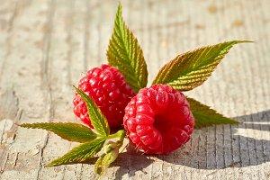Fresh raspberries vith leaves on wooden table.