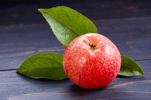 Red ripe and juicy apple with leaves.