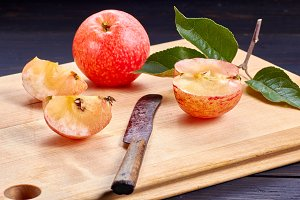 Very ripe and juicy apple with slices on wooden cutting board