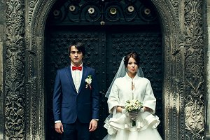 Bride and groom behind an old door