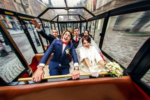 Newlyweds sit in a tourist tram