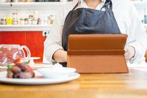 Woman using pad at cafe counter