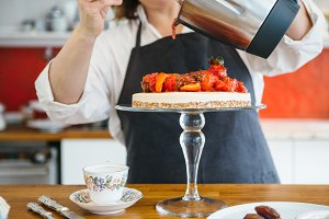 Woman decorates cake with strawberry