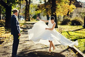 Bride spreads her dress in the park