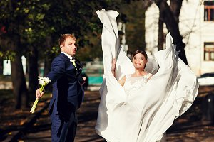Happy newlyweds jump in the park