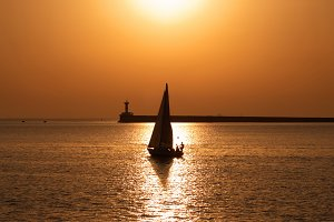 Sail boat against sea sunset