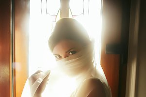 Bride looks mysterious behind a veil