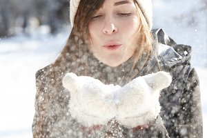 Young woman blowing snowflakes off her hands