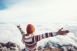 Happy woman traveler over clouds