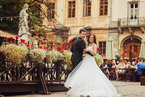 Groom holds bride's waist posing