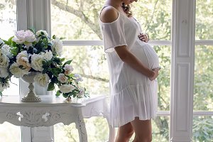 young pregnant woman in white dress in the studio