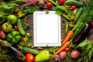 Tablet surrounded fresh vegetables