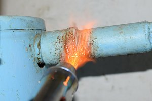 Heating a steel pipe with a blowtorch. The flame of a blowtorch
