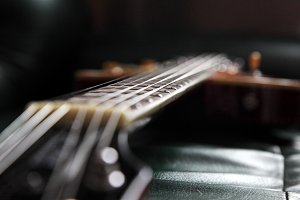 Guitar in dark room, shallow depth of field. Natural lightning.
