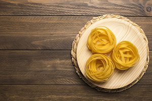 Spaghetti on wooden bowl. Copy space. Horizontal shoot.