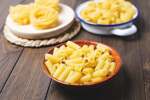 Kitchen containers with macaroni and spaghetti about to cook on wooden table. Horizontal shoot.