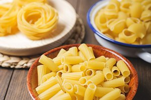 Close-up of kitchen containers with macaroni and spaghetti about to cook on wooden table. Vertical shoot.