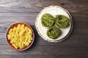 Macaroni and vegetable spaghetti on wooden table.