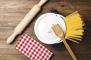 Spaghetti inside a pot next to a wooden fork and a roller on wooden table. Vertical shoot.