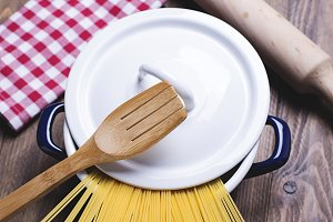 Spaghetti inside a pot next to a wooden fork and a roller. Vertical shoot.