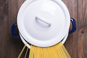 Spaghetti inside a pot on wooden table. Vertical shoot.